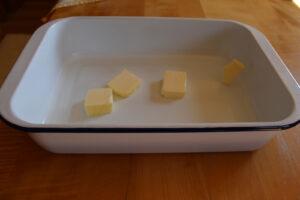Form wird mit Butter befettet für die Buchteln.